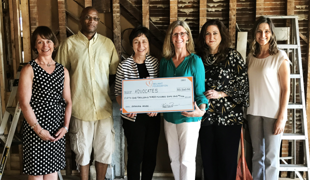 Group of six people standing in a room under renovation; two are holding a large presentation check